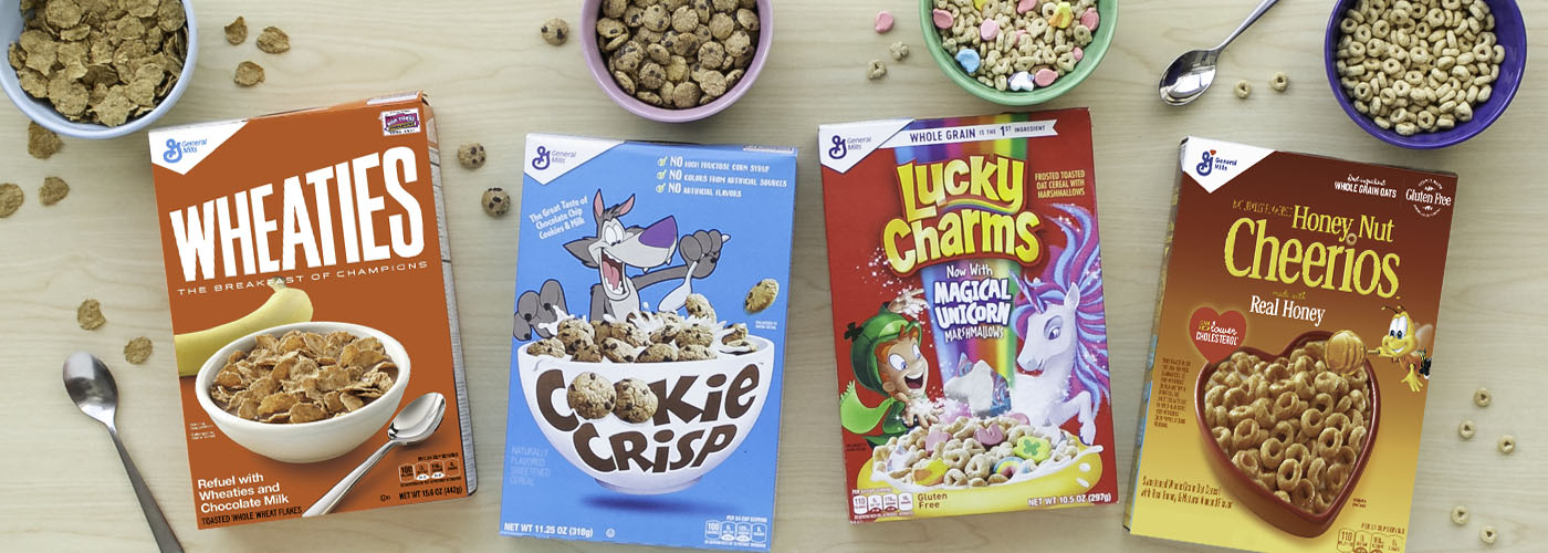 Four boxes and bowls of General Mills cereal